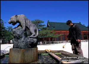 Estudante lava as mãos em santuário em Heian.